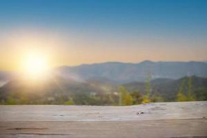 Table en bois vide pour produit actuel avec forêt naturelle flou doux avec fond de montagne photo