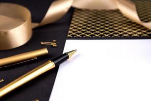 Trombones ruban stylo or et papeterie sur fond noir avec une feuille de papier blanc avec espace de copie photo