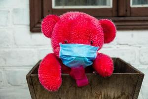 Ours en peluche rouge solitaire dans un masque médical de protection photo