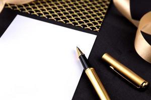 stylo or, ruban, trombones et papeterie sur fond noir avec une feuille de papier blanc avec espace copie photo