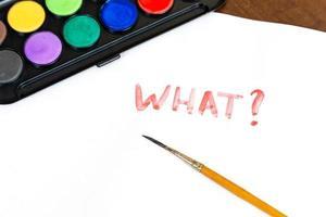 manuscrite quel texte avec pinceau et peintures à l'aquarelle sur fond blanc photo