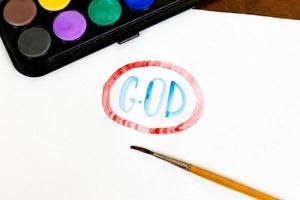 Texte de Dieu manuscrit avec pinceau et peintures à l'aquarelle sur fond blanc photo