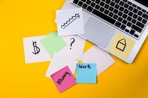 Espace de travail de bureau à domicile avec ordinateur portable et papier autocollant sur fond jaune photo