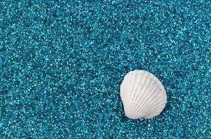 Coquillages blancs disposés sur un fond de paillettes bleu aqua à la mode photo