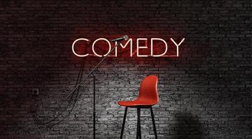 scène éclairée par un projecteur et une lampe néon rouge avec le mot comédie photo