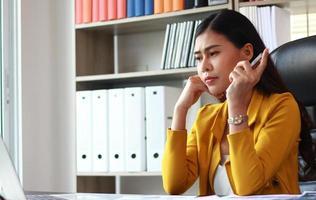 Portrait de femme asiatique en costume jaune assis au bureau en pensant au marketing photo