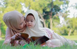 mère musulmane apprend à sa fille à lire joyeusement le coran dans le parc en été photo