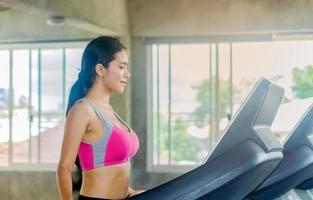 belle femme asiatique exerce dans une salle de sport photo