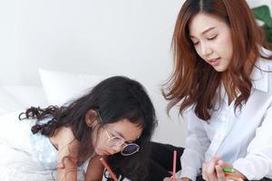 mère asiatique enseigne ses devoirs à sa fille à la maison en vacances photo