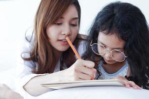 mère asiatique enseigne ses devoirs à sa fille à la maison photo