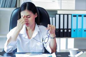 femme d'affaires asiatique fatiguée et ayant la fatigue oculaire de travailler dur photo