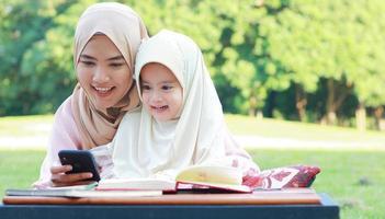 mère et fille musulmane profitant de leurs vacances dans le parc photo