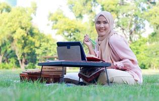 belle fille musulmane assise joyeusement dans le parc photo