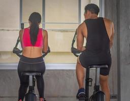 belle femme asiatique exerce dans une salle de sport avec un entraîneur personnel photo