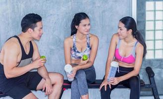 les jeunes parlent après l'exercice dans la salle de sport, le concept de l'exercice et la pratique du sport pour la santé photo