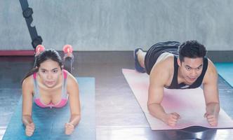 les jeunes font des exercices dans la salle de gym photo