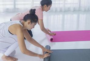 les femmes asiatiques préparent le yoga au gymnase photo