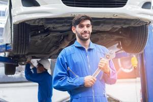 techniciens au centre de service de voiture stand avec des outils et prêts à fournir des services professionnels photo