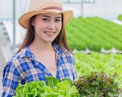 Portrait d'une femme asiatique tenant un panier de légumes frais et de légumes biologiques photo