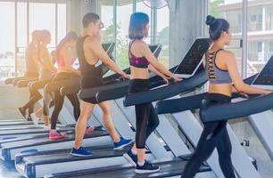 jeunes exercices de groupe dans la salle de gym en faisant du jogging sur le tapis roulant photo
