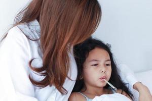 mère asiatique mesurant la température de sa fille photo