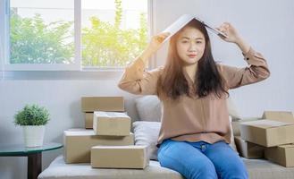 belle femme asiatique assise à la maison et travaillant en ligne, entreprise d'expédition en ligne photo