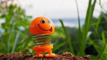 une photo d'une poupée jouet orange avec une expression souriante