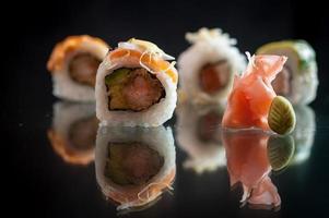 morceaux de sushi sur fond noir avec son reflet photo