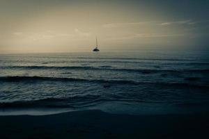 bateau flottant sur la plage au coucher du soleil photo