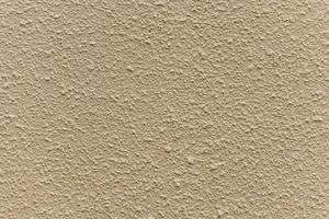 Mur de maison en plâtre rugueux beige clair comme arrière-plan photo