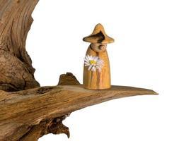 Gnome en bois tourné avec une marguerite à la main se dresse sur une vieille souche d'arbre photo