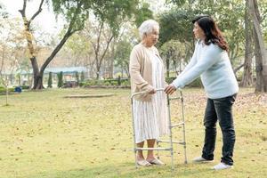 Aide et soins asiatique senior ou vieille dame âgée utiliser marcheur avec une bonne santé tout en marchant au parc en joyeuses vacances fraîches photo