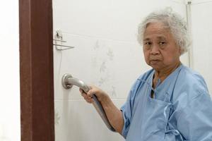 Senior asiatique ou âgée vieille dame femme patient utiliser la sécurité de la poignée de salle de bains de toilettes en salle d'hôpital de soins infirmiers photo
