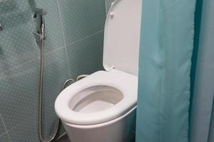 Cuvette en céramique à chasse d'eau avec rideau vert dans la salle de bain photo