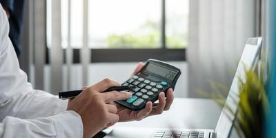 Close up business woman using calculator and laptop for do math finance on wood desk in office and business working background statistiques de comptabilité fiscale et concept de recherche analytique photo