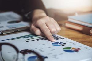 femme d & # 39; affaires pointant vers des graphiques montrant le marché de l & # 39; investissement photo