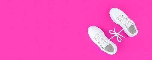 Paire de chaussures de sport blanches connectées avec des lacets bow sur fond rose plat simple poser avec copie photo