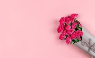 Bouquet de petites roses à fleurs enveloppées dans du papier kraft sur fond rose avec copie espace photo