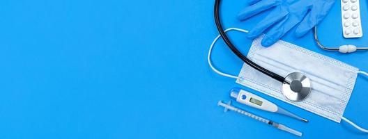 Masque facial stéthoscope pilules thermomètre seringue médicale blister et gants médicaux sur fond bleu bannière plate avec espace copie photo