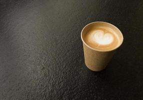 Tasse de café artisanal avec espace copie en forme de coeur sur une table texturée noire photo