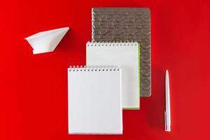 Fournitures de bureau - cahiers et stylos sur fond rouge photo