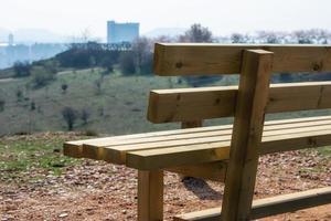 Fermer banc en bois vide dans le parc du printemps sur la ville photo
