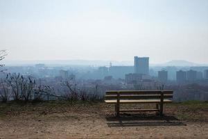 Banc en bois vide dans le parc du printemps sur la ville photo