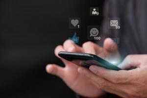 Personne utilisant le concept d'interactions de réseau de médias sociaux smartphone avec des icônes de commentaires photo