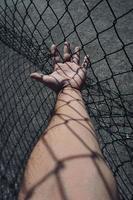 main atteignant une clôture métallique photo