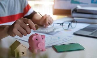 homme d & # 39; affaires mettant l & # 39; argent dans la tirelire pour économiser le concept de comptabilité financière photo