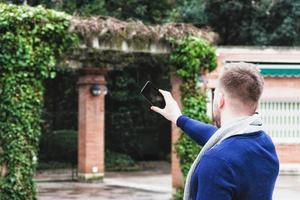 jeune homme, dos à la caméra, prendre une photo avec son téléphone portable