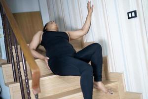 Asiatique femme d'âge moyen femme patient tomber dans les escaliers parce que les surfaces glissantes photo