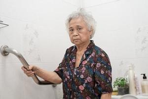 Senior asiatique ou âgée vieille dame femme patient utiliser la sécurité de la poignée de passerelle de pente avec aide assistant de soutien en salle d'hôpital photo