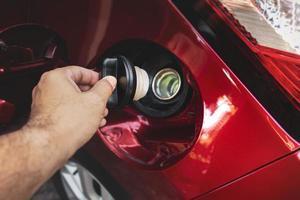 la main humaine tient le bouchon du réservoir de carburant de la voiture pour ouvrir ou fermer photo